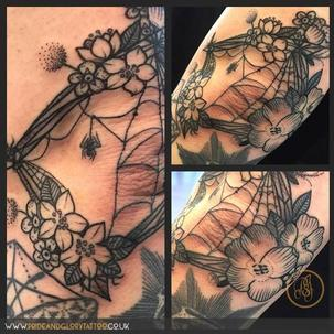 Black work flowers and spider web frame elbow black tattoo by Chessie Clear at Pride and Glory tattoo studio, Leigh-on-sea Essex, Uk.