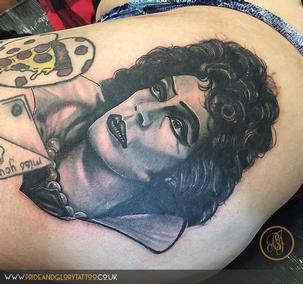 Frank 'N Furter Rocky Horror Show black and grey realistic portrait thigh tattoo by Chessie Clear at Pride & Glory tattoo studio, Leigh-on-sea, Essex, UK