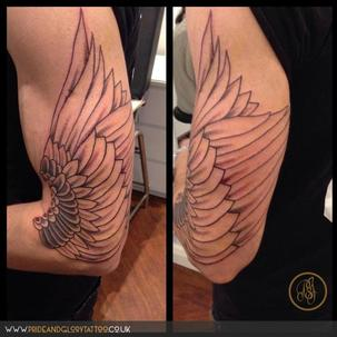 Freehand wing tattoo on upper arm by Chessie at Pride & Glory