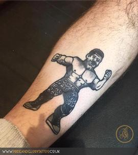 Ravishing Rick Rude traditional tattoo of a retro wrestling toy by Chessie Clear at Pride and Glory tattoo studio, Leigh-on-sea. Essex, UK